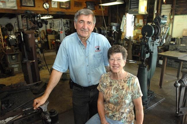 Bud and Janelle Harvey pose for a portrait in the well-equipped blacksmith shop behind their Chillicothe home. Bud took his first blacksmith class several years before retiring from Caterpillar where he worked as at metalurgical engineer.